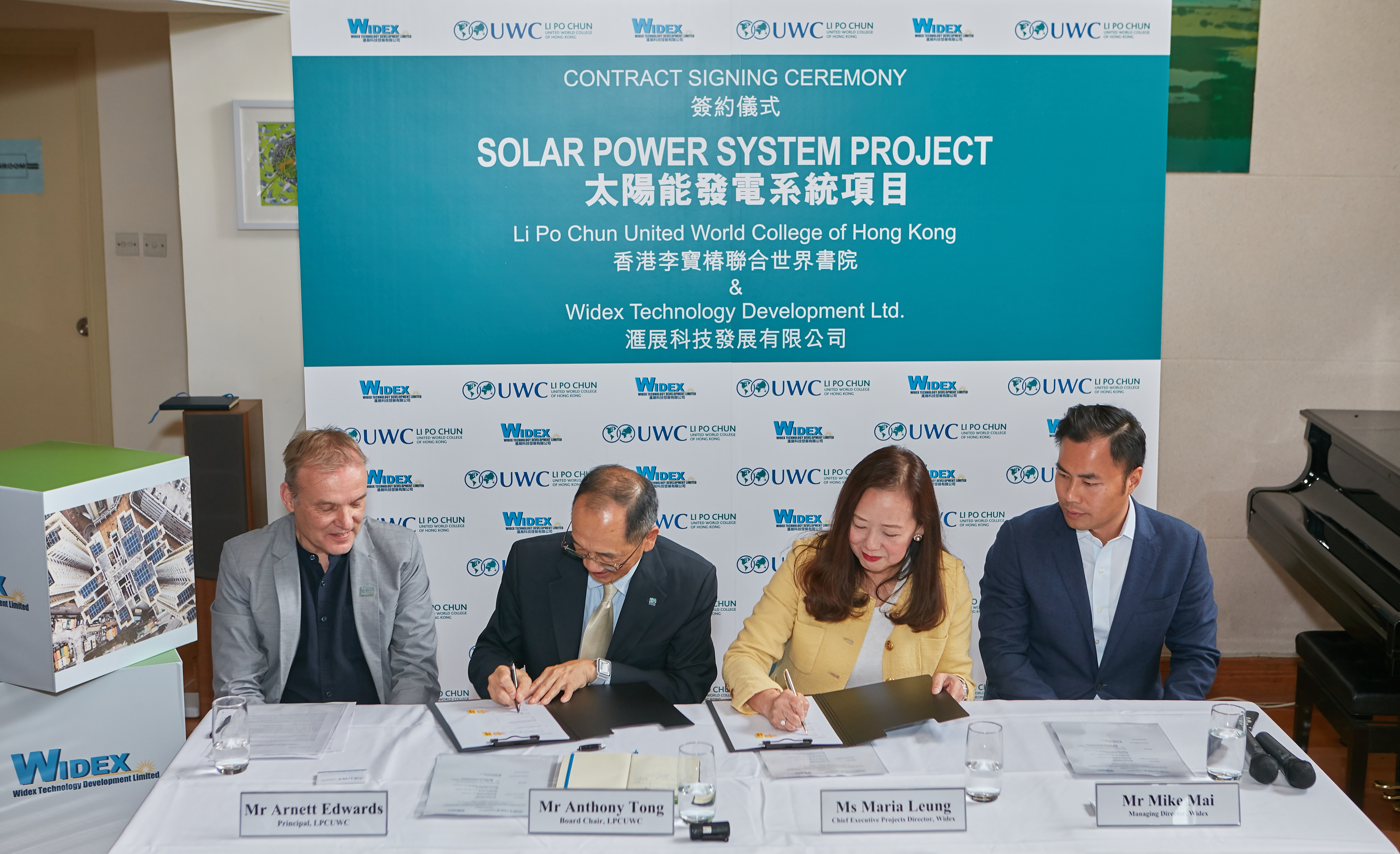 PHOTO: LPCUWC Board Chair Anthony Tong, second from left, signs the contract on the solar power system project on campus, with Widex Chief Executive Projects Director Maria Leung. Looking on are LPCUWC Principal Arnett Edwards, first from left, and Widex Managing Director Mike Mai.